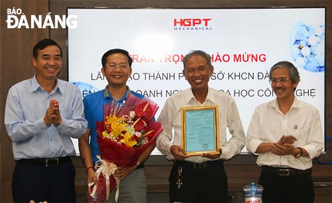 Phó Chủ tịch UBND thành phố Lê Trung Chinh(bìa trái)cùng lãnh đạo Sở Khoa học và Công nghệ (bìa phải) trao giấy chứng nhận doanh nghiệp khoa học và công nghệ cho Công ty CP Cơ khí Hà Giang Phước Tường tháng 11-2019.